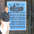 Mick next to the calendar of performances at The Jacaranda