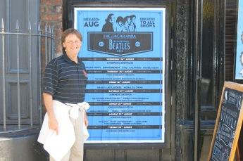 Mick next to the calendar of performances at The Jacaranda